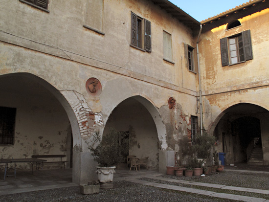"""An old """"cascino"""" back alongside the Naviglio Pavese, at the turnoff to Zibido. Leonardo spent time here. I think Angelo said it was """"San Lorenzo"""". In the inner courtyard, there are bas-relief busts jutting from the walls of various people."""